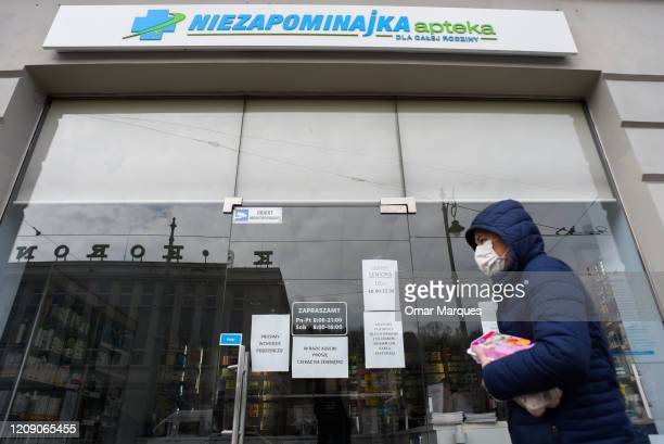 A man wears a protective mask as he walks in front of a pharmacy during the declared state of pandemic by the government on April 03 2020 in Krakow...
