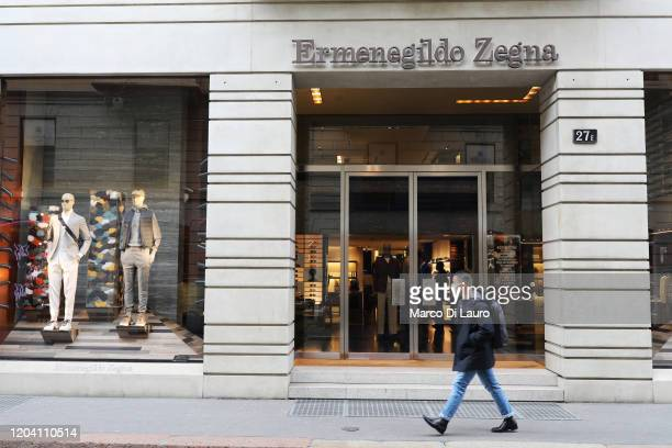 Man wears a protective mask as he walks in front of the Ermenegildo Zegna store in Via Montenapoleone, the most important road of the fashion...