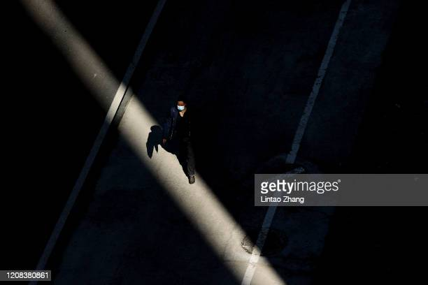 A man wears a protective mask as he walks through the shadows from inbetween two buildings on March 27 2020 in Beijing China The Coronavirus pandemic...