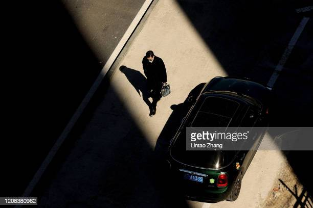 Man wears a protective mask as he walks through the shadows from inbetween two buildings on March 27, 2020 in Beijing, China. The Coronavirus...