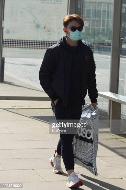 Man wears a protective mask as he walks through the streets of Sheffield, England on 24 March 2020.