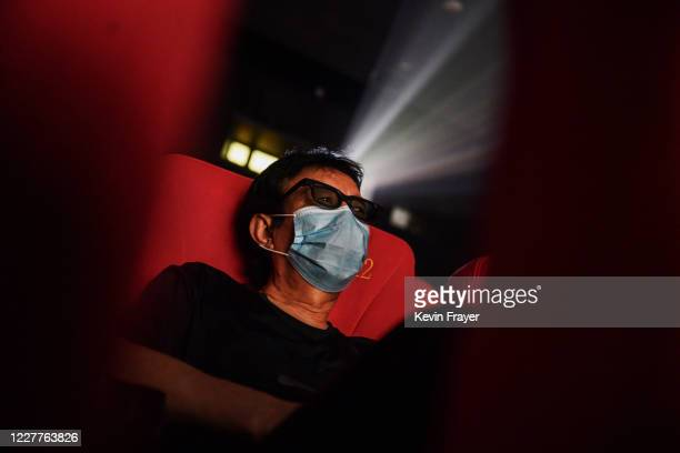 A man wears a protective mask as he watches a movie in 3D at a theatre on the first day they were permitted to open on July 24 2020 in Beijing China...