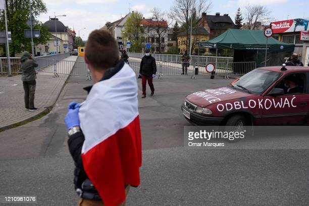 A man wears a protective mask as he wears a Polish flag around him during a protest against the ongoing closure of the Polish Czech border which was...