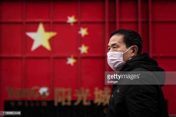 A man wears a protective mask as walk in street on February 10 2020 in Wuhan China2020 in Wuhan Hubei provinceChina Flights trains and public...