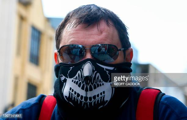 A man wears a protective mask following the outbreak of the novel coronavirus COVID19 in Cardiff Wales on March 14 2020 British Prime Minister Boris...