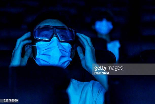 A man wears a protective mask while watching a movie in 3D at a theatre on the first day they were permitted to open on July 24 2020 in Beijing China...