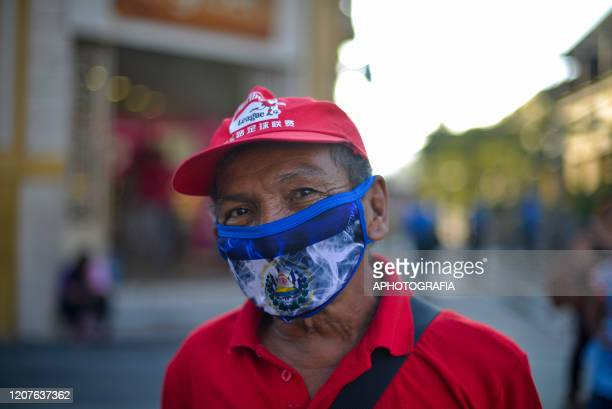 A man wears a protective mask with the flag of El Salvador as he walks through the streets of downtown on March 18 2020 in San Salvador El Salvador...