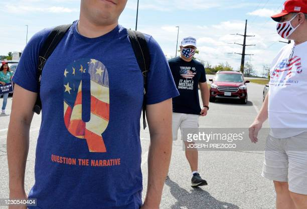 Man wears a QAnon shirt while boarding a shuttle bus at the Manchester Mall going to Manchester Airport in Londonderry, New Hampshire on August 28,...
