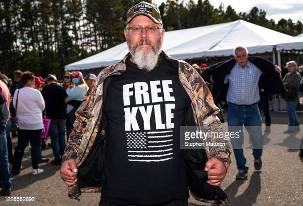 """Man wears a shirt that says """"Free Kyle"""", referencing Kyle Rittenhouse, during a rally for President Donald Trump at the Bemidji Regional Airport on..."""