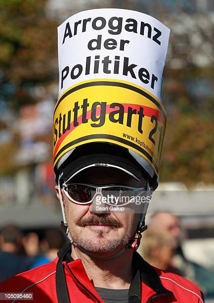 A man wears a sign on his head that reads 'The Arrogance of Politicians' among tens of thousands of activists marching to protest the Stuttgart 21...