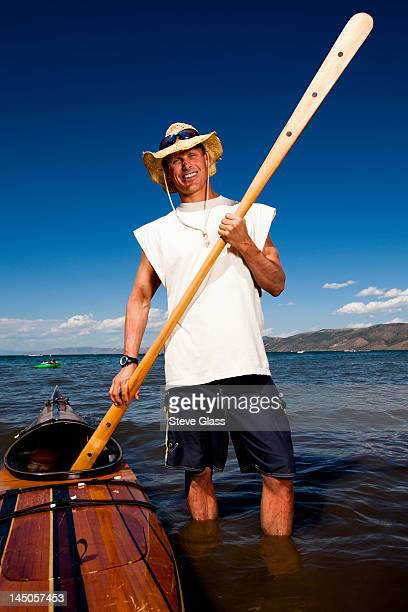 A man wears a straw hat as he poses for a portrait with a wooden kayak and paddle that he made while standing on the shore of Bear Lake, Utah.