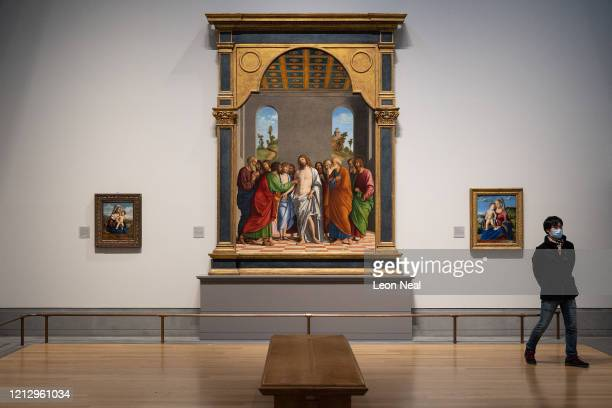 """Man wears a surgical mask as he walks away from """"The Incredulity of Saint Thomas"""" by Conegliano at the National Gallery on March 17, 2020 in London,..."""