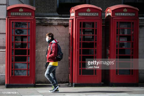 A man wears a surgical mask as he walks past a row of iconic London telephone boxes on March 17 2020 in London England Boris Johnson held the first...