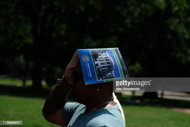 A man wears a tourism guide on his head to stay cool near the White House during an excessive heat wave on July 20 2019 in Washington DC An excessive...