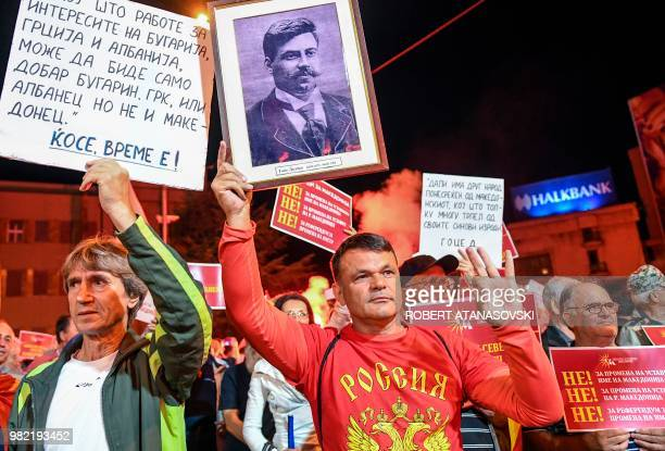 A man wears a tshirt lettering Russia and holds a picture with Macedonian national hero Goce Delcev in front of the parliament building in Skopje on...