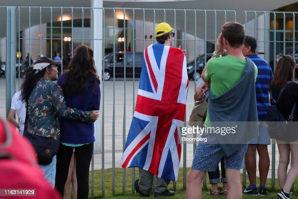 A man wears a Union flag also known as a Union Jack as people watch the arrival of UK Prime Minister Boris Johnson at the Chancellery in Berlin...