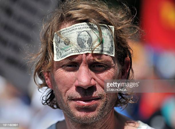 A man wears a US dollar bill on his forehead during a demonstration near the Time Warner Cable Arena on September 2 2012 in Charlotte North Carolina...