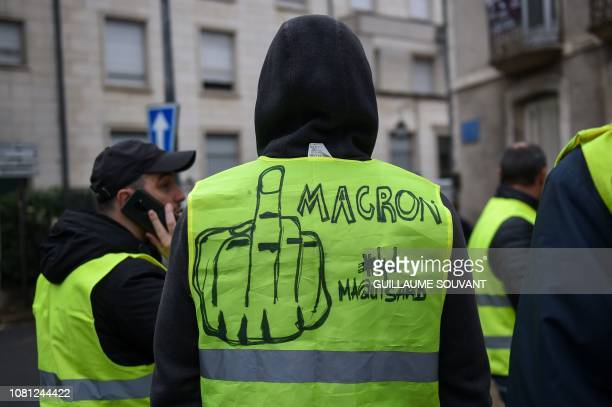 A man wears a yellow vest on which is written 'Macron ' next to a drawing of a finger during an antigovernment demonstration called by the Yellow...