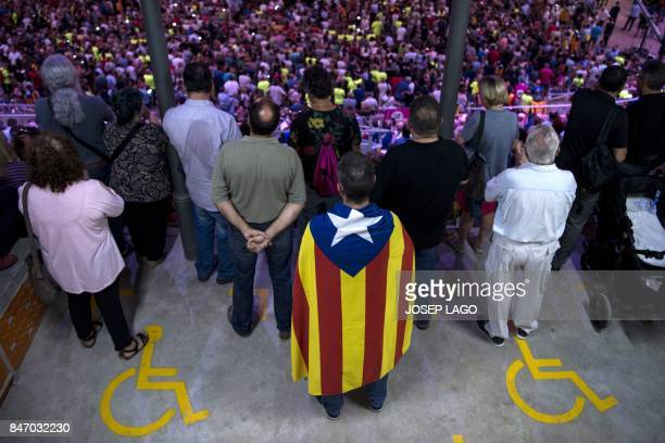 A man wears an 'Estelada' at the Tarraco arena in Tarragona during the official launch of the Catalan main separatist parties' campaign for an...