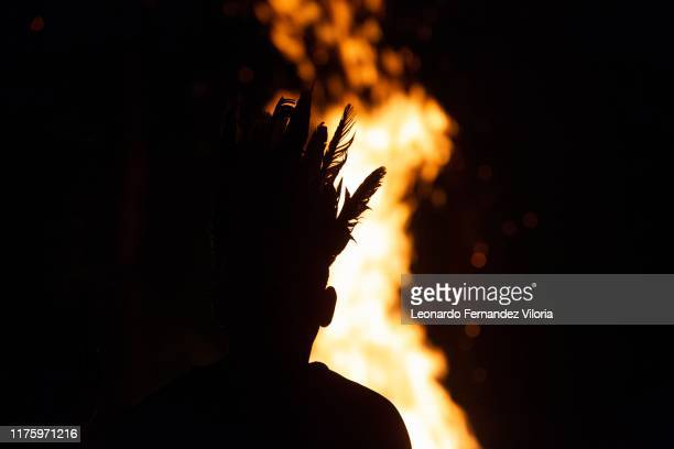 A man wears an indigenous crown with feathers in the celebration Baile de la Candela during the congregation of thousands of people following the...