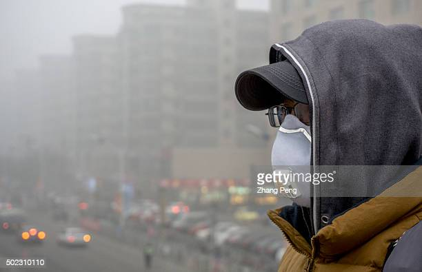 A man wears antitoxic mask to protect from breathing poisonous air Since December Beijing has suffered continuously three severe haze hazard