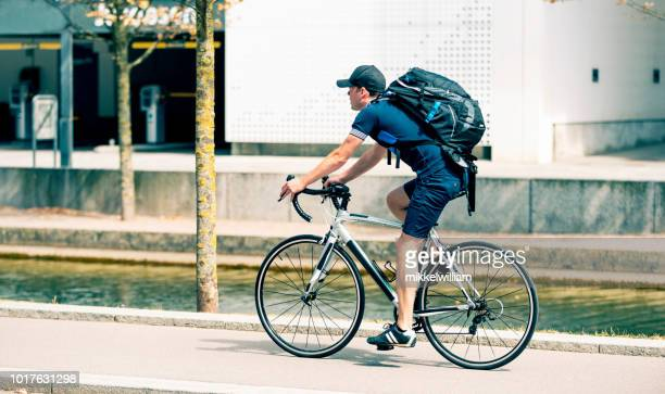 Man wears backback and commutes to work on bicycle