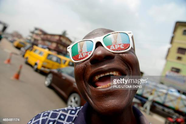 A man wears branded sun glasses of opposition All Progressives Congress during a rally christened 'Walk for Change in Lagos on March 7 to drum...