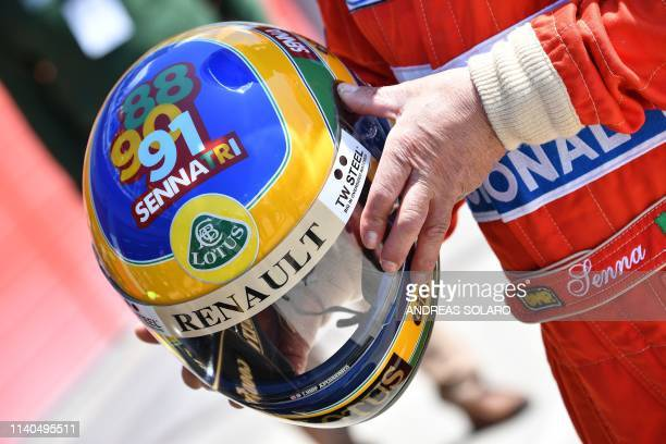 A man wears Brazilian's F1 driver Ayrton Senna's helmet and suit on May 1 2019 at the Imola Enzo and Dino Ferrari circuit during a tribute ceremony...