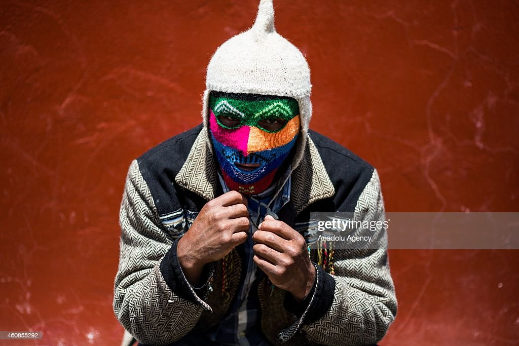 A man, wears colorful mask poses during Takanakuy celebrations in the region of Chumbivilcas, Cuzco in the Andes of southern Peru on December 25, 2014. The Takanakuy is a traditional celebration held every December 25. The celebration can last many days. The word 'Takanakuy' means 'to strike with the fist' and fighters are heating with dances and songs called Wayliyas. Men and women who have had problems with other people during the year are fixing their conflicts at the end of the year with one or several fights. Usually, conflicts are raised by issues related to land or harvesting, stealing animals or insulting the name of the father. Some collisions are caused by love or friendship issues.