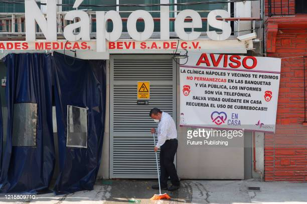A man wears face mask as precautionary measure while sweep the entrance of the Naples clinic amid the new virus pandemic on May 27 2020 in Mexico...