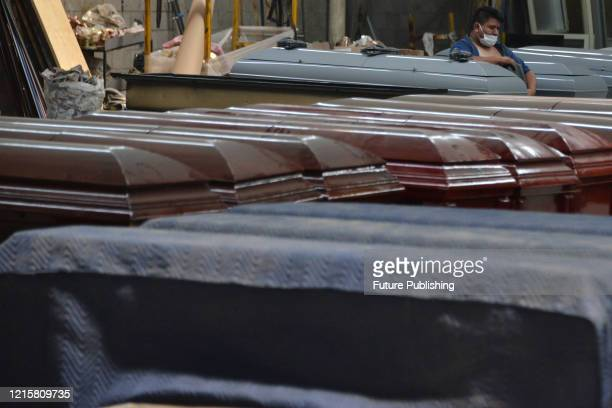 Man wears face mask as precautionary measure while works in the manufacture of a steel coffin made to closed it hermetically, specially design to...