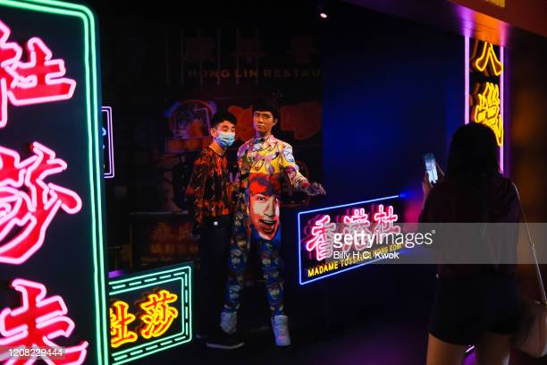 A man wears face masks as a precaution against the spread of Coronavirus taking pictures with the waxfigure of singer Leo Koo during a coronavirus...
