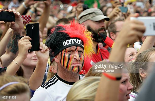 A man wears face paint while supporting the German national soccer team in front of the Brandenburg Gate on July 15 2014 in Berlin Germany Thousands...