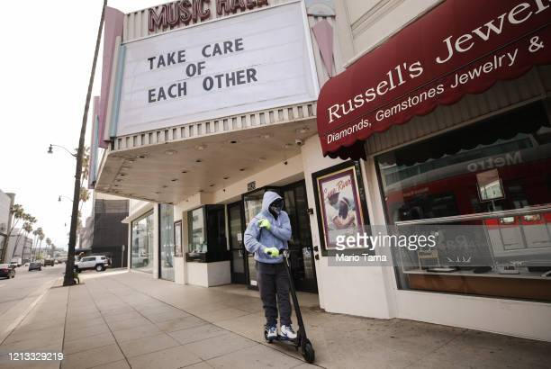 A man wears gloves and a bandanna across his face while riding a scooter past a shuttered movie theater with the message 'Take Care of Each Other'...