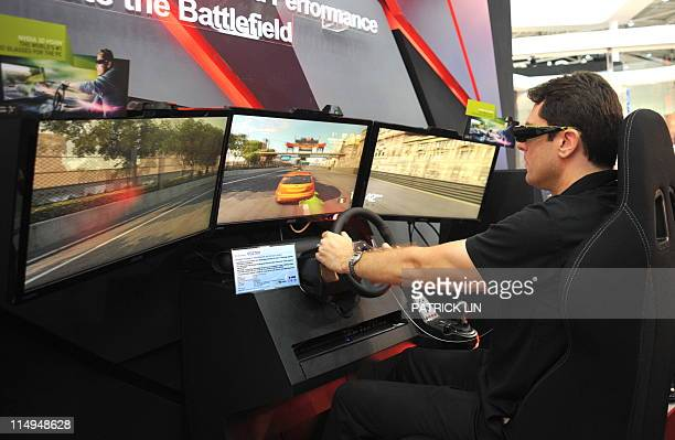 A man wears goggle while playing a threedimentional game on a gadget developed by AsusTek Computer Taiwan's leading computer brandname after the...