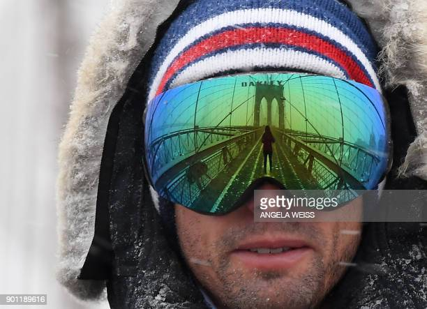 TOPSHOT A man wears googles reflecting the Brooklyn Bridge on January 4 2018 in Brooklyn New York The US National Weather Service warned that a major...
