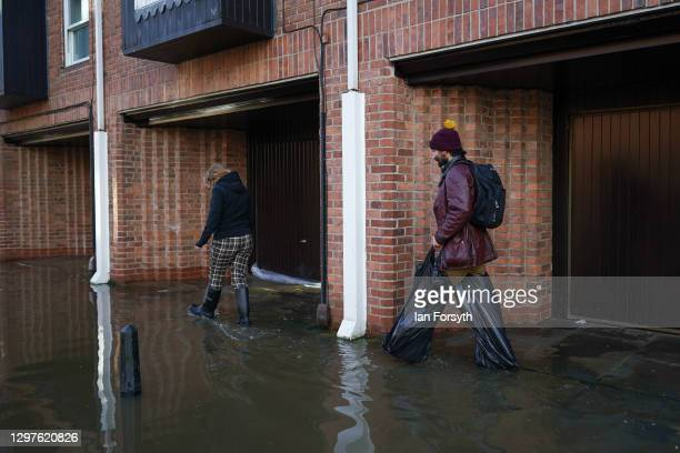 Man wears improvised waders as he walks through flood water after the River Ouse in York floods following rain and melting snow on January 21, 2021...