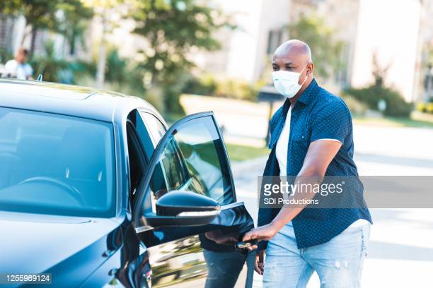 man wears mask to drive car during coronavirus epidemic - mid adult men stock pictures, royalty-free photos & images