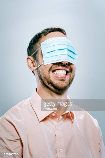 man wears  protective face mask over his eyes instead of mouth - careless stock pictures, royalty-free photos & images