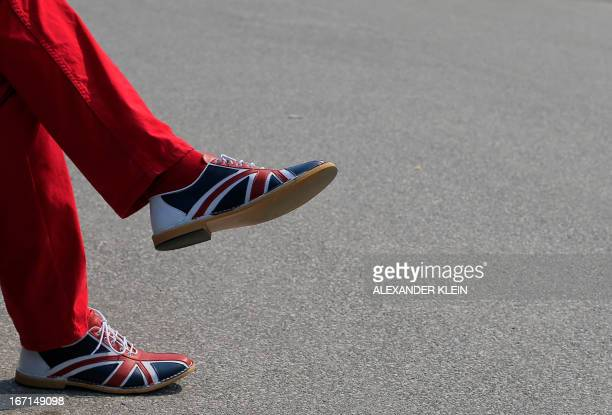 Man wears red trousers with shoes with a Union Jack motif on a sunny day in Vienna on April 21, 2013. AFP PHOTO / ALEXANDER KLEIN