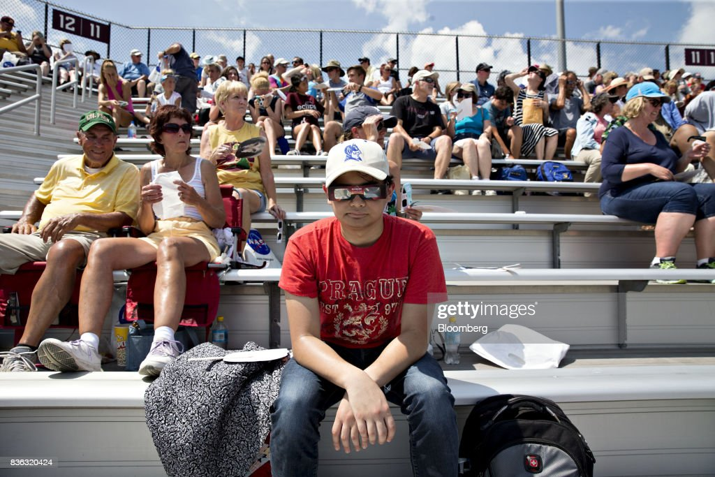 A man wears solar viewing glasses while sitting in the stands during a solar eclipse viewing event on the campus of Southern Illinois University (SIU) in Carbondale, Illinois, U.S., on Monday, Aug. 21, 2017. Millions of Americans across a 70-mile-wide (113-kilometer) corridor from Oregon to South Carolina will see the sky darken as the sun disappears from view total during the eclipse, with Carbondale seeing totality for 2 minutes and 38 seconds. Photographer: Daniel Acker/Bloomberg via Getty Images