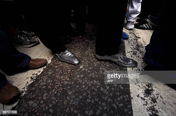 A man wears sparkling shoes as he crosses Abbey Road on August 8 2009 during an event to celebrate 40 years to the minute since the Abbey Road album...
