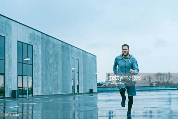 Man wears sports clothes and runs fast outside after rain
