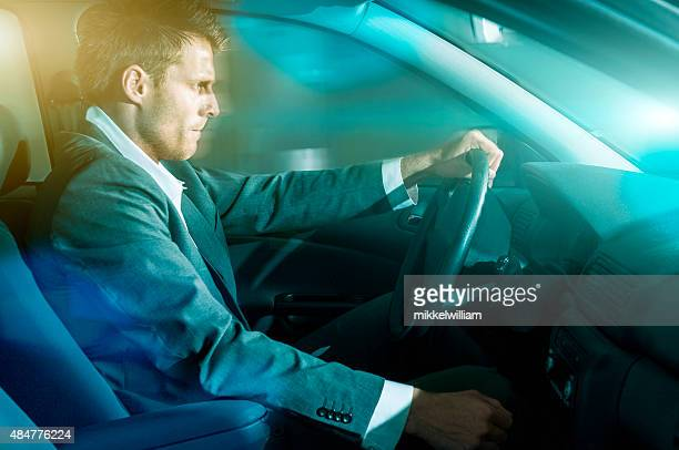 Man wears suit and drives car at night