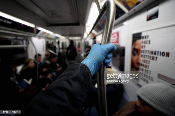 Man wears surgical gloves to prevent Covid-19 spread, at the New York City subway train in New York, United States on March 11, 2020.