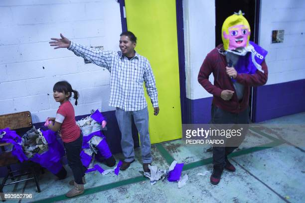A man wears the head of a pinata with the figure of US President Donald Trump during a traditional posada in Mexico City on December 16 2017 The...