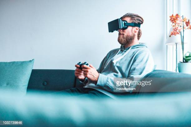 Man wears virtual reality glasses and controls a game with handheld controller