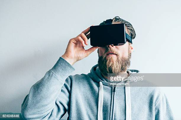 Man wears VR glasses and adjusts the content