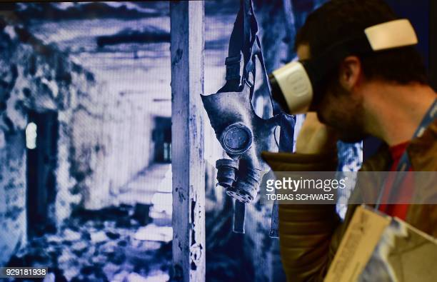 A man wears VR glasses at a booth promoting VR pictures of Chernobyl during the International Tourism Trade Fair in Berlin on March 8 2018 The...