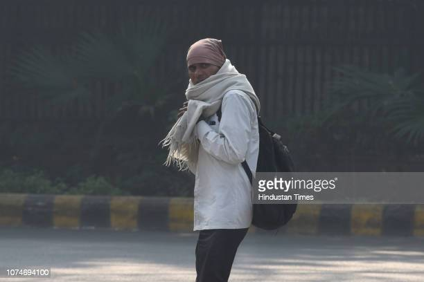 A man wears warm clothes to protect himself from cold on a winter morning at Gol Dak Khana road on December 23 2018 in New Delhi India The national...